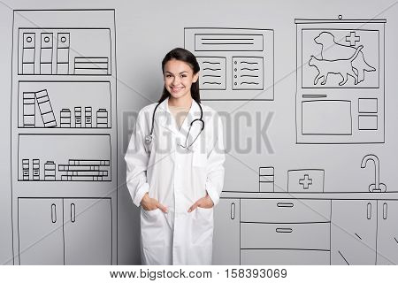 I love my profession. Beautiful young ambitious doctor posing while standing on a grey background and smiling.