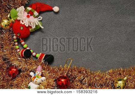Christmas background for an inscription. On a gray velvety red background Santa Claus and snowman tinsel. Space for text. New Year's background. texture card