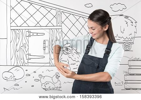 Work for pleasure. Happy cheerful young farmer woman holding chicken and smiling while standing in the yard.
