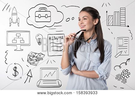 Delighted and calm. Young pretty overjoyed woman holding glasses and smiling after working in an office.