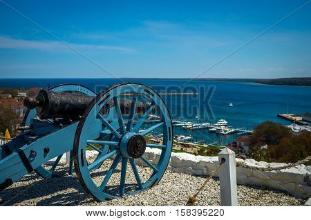 a blue cannon overlooks the lake at Fort Mackinac