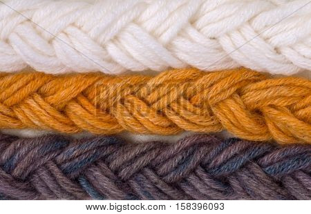 Braided wool yarn swatches colored by henna and indigo and control white sample