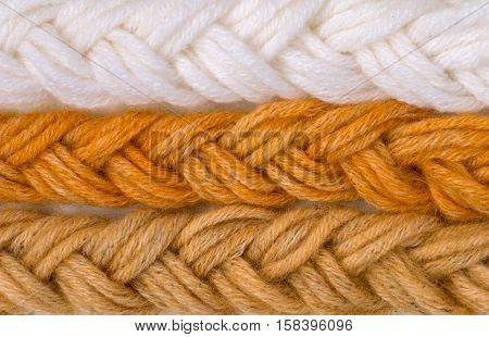 Braided wool yarn swatches colored by henna and henna and amalaki mix and control white sample