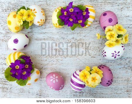 Colorful easter eggs and primrose violet and yellow flowers composition