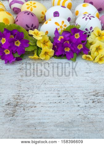 Yellow and violet Easter eggs and primrose flowers bouquet composition