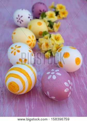 Easter Eggs And Primrose Bouquets On The Violet Board
