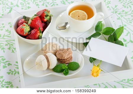 Healthy beautiful breakfast in bed of green tea strawberries sweets and yellow rose envelope on a white tray. Beautiful breakfast in bed on white tray and yellow rose under envelope. Horizontal.
