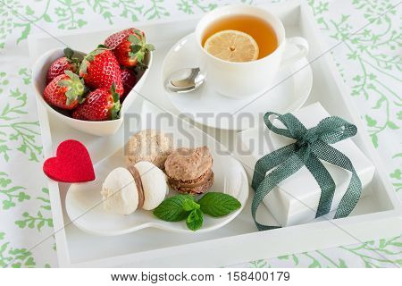 Breakfast in bed of green tea strawberries sweets and gift box on a white tray. Romantic breakfast in bed and gift with love concept. Horizontal. Daylight. Close up.
