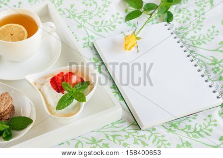Wake up with breakfast in bed near empty notebook and yellow rose on it. Day planning breakfast notebook concept. Horizontal. Close up.