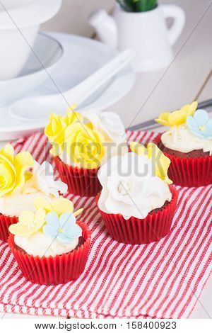 cupcakes decorated with cream cheese and flower fondant
