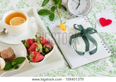 Breakfast in bed of green tea strawberries sweets on a white tray next to gift box yellow rose envelope with heart alarm clock. Romantic breakfast in bed and gift with love concept. Horizontal.
