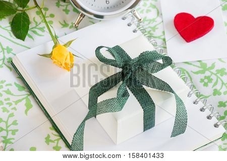 Gift box yellow rose envelope with heart alarm clock. Romantic gift love confession concept. Horizontal. Daylight. Close