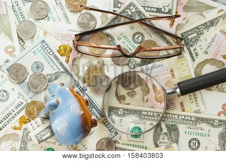 Different collector's coins and banknotes with a magnifying glass glasses and piggy bank wooden background