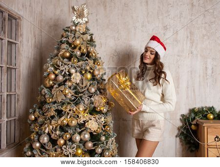 young attractive brunette woman with gift box near Christmas tree in cosiness home interior
