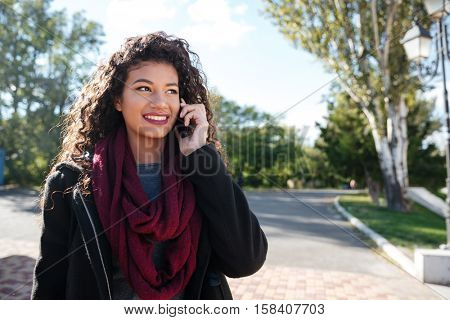 Portrait of attractive dark-skinned young woman dressed in sweater and scarf talking at phone. Against nature background. Look aside.