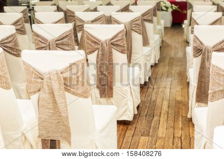 Indoors wedding reception venue with decor, selective focus on chair
