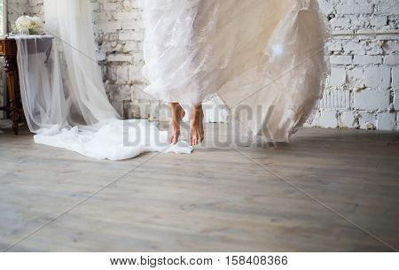 Bride jumping barefoot in rustic white wedding dress. Beautiful wedding gown. Loft style wedding.