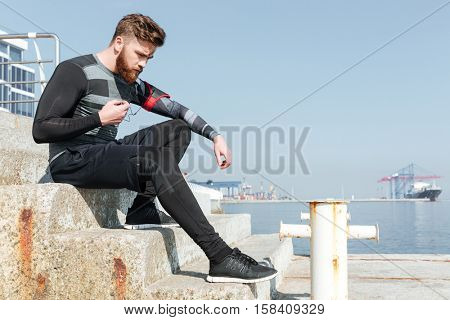 Serious runner sitting on stairs near the sea. looking down. side view