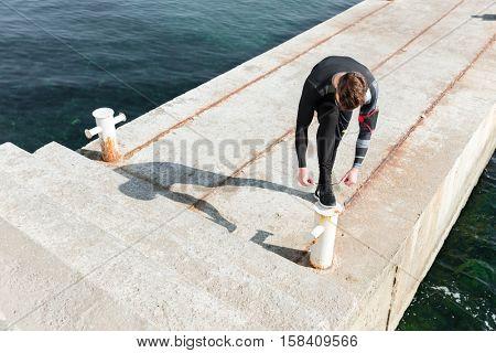 Top view of runner near the sea. tying shoelaces. preparing
