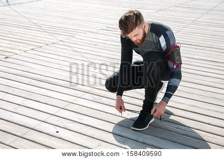 Top view of young runner preparing the sea. tying shoelaces