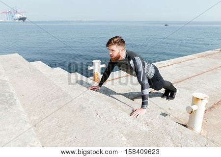 Male doing push ups near the sea. on stairs. top view