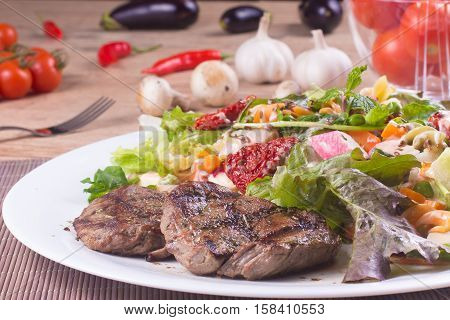 Fillet Mignon with Fresh and healthy Salad over a wooden table