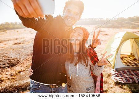 Young smiling happy couple making selfie while standing at campsite