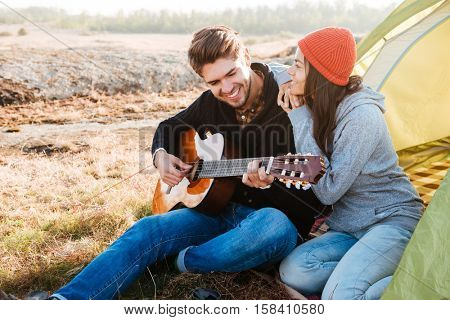 Portrait of a happy couple with guitar having camping with tent outdoors