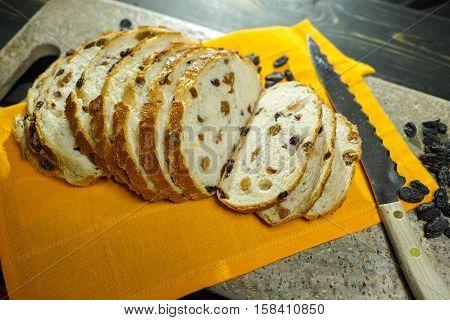 Fresh baked raisins bread sliced on granite board