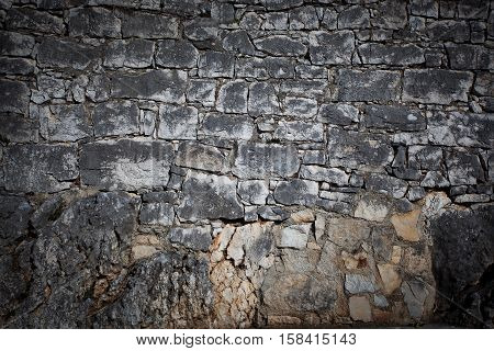 Old city wall built of large stones gray