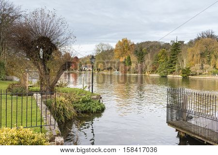 An Autumnal image of the River Thames flowing through Henley On Thames Oxfordshire England UK