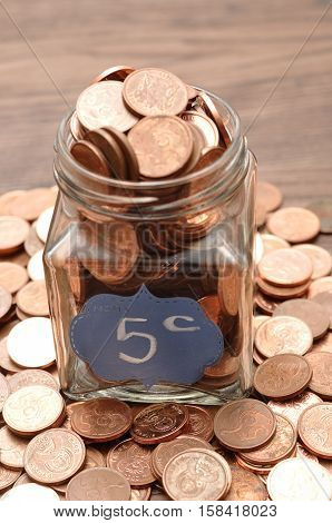 A bottle filled with five cents South African coins