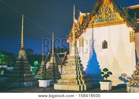 Wat Pho in night, Bangkok, Thailand. Wat Pho known also as the Temple of the Reclining Buddha. Bright lights of a Buddhist Temple.