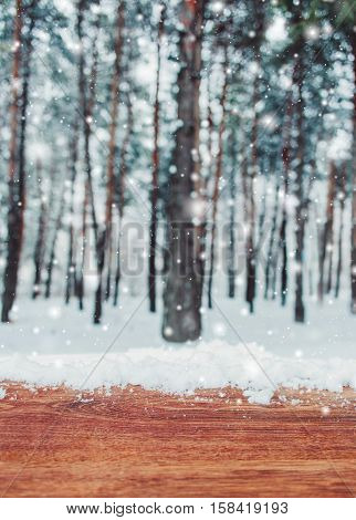 Christmas background with fir trees and blurred background of winter with wooden table with snow place. Frosty winter landscape in snowy forest