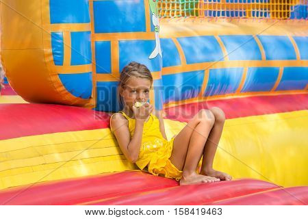 Girl Eats An Apple Sitting On The Edge Of The Inflatable Trampoline In Amusement Park