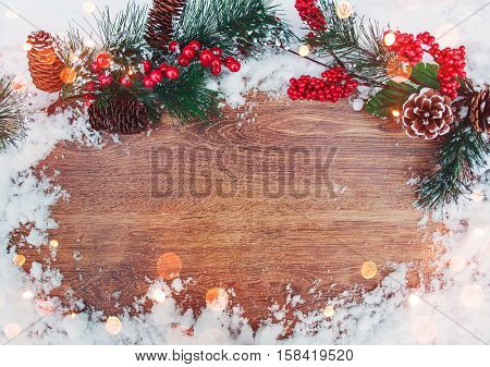 Christmas decoration branch of fir tree with cones and snow on wooden background.Merry Christmas and Happy New Year theme