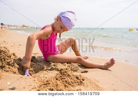 Girl Digs A Hole In The Sand On The Beach