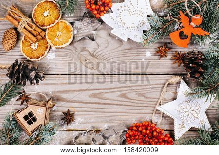 christmas or new year background. Fir branches, Christmas toys, cinnamon and oranges on the wooden background