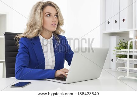 Dreamy businesswoman in blue blazer is typing and staring into distance. Concept of daydreaming and being not concentrated