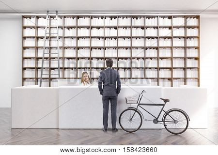 Man is standing in a library near a counter and talking to an employee. A bike is standing beside him. 3d rendering. Mock up