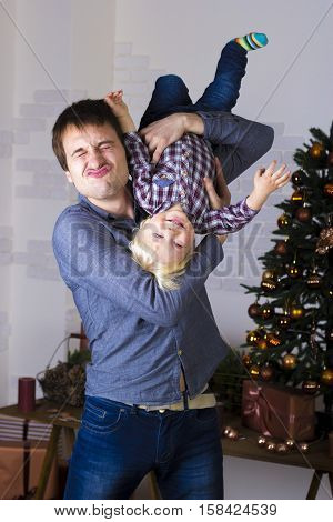 Father and son fooling around at the Christmas tree with gifts