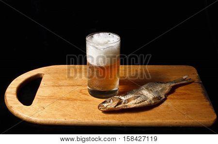 Glass of beer and salty fish Pelecus cultratus top view.