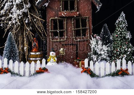 miniature Christmas scene with rustic house and decorated white picket fence in deep snow with snowman and pine trees