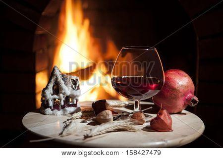 A glass of brandy, candle, pomegranate burning fireplace