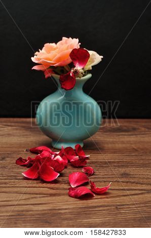 A blue vase with rose where one has lost its petals. Shallow dept of field