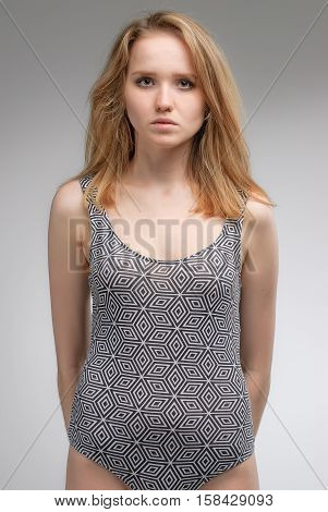 Young beautiful fashionable deplorable model over grey background. Side view