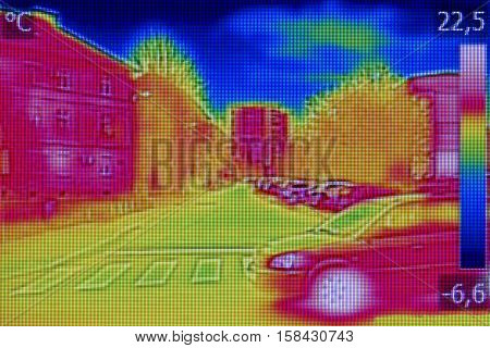 Infrared thermovision image showing lack of thermal insulation on Residential building and cars on the street