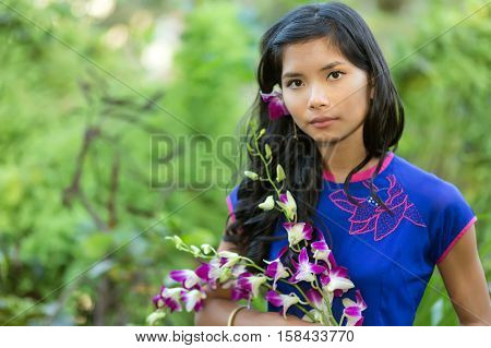 Pretty Vietnamese woman wearing a traditional Ao Dai dress and holding orchid flower bunch