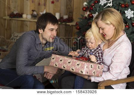 Young family unwraps Christmas gifts near Christmas tree