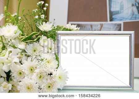 Blank vintage photo frame and flower on wooden background.